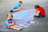 Photo three little children, two school kids boys and toddler girl having fun with with car picture drawing with colorful chalks on asphalt. Siblings painting on ground playing together. Creative leisure