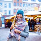 schöne junge Frau beim Verzehr von mit weißer Schokolade überzogenen Früchten am Spieß auf dem traditionellen deutschen Weihnachtsmarkt. glückliches Mädchen auf dem traditionellen Familienmarkt in Deutschland, Berlin bei verschneitem Tag.
