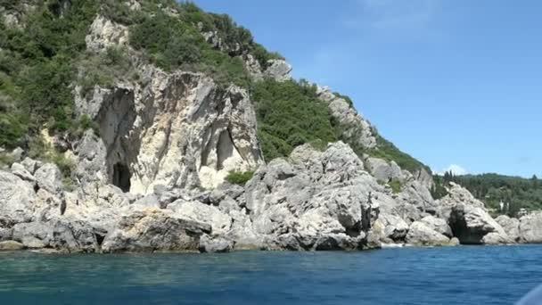 Bootsfahrt von Paleokastritsa in Richtung Liapades Beach auf Korfu (Griechenland). Weitergabe von Sediment Kreidefelsen im Wasser. Kliffküste mit Wald.