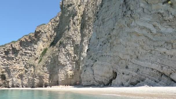 Liapades, Corfu / Griechenland 1. Juni 2018: fahren mit einem Boot lange Paradies Strand Teil nennt Chomi Strand von Liapades auf Korfu (Griechenland). Sedimentären Felsen der Kreidefelsen. Boot am Ufer.