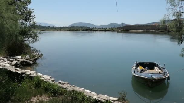 boat on the shore of Vivari Channel in Buthrotum, also known as Butrint (Albania) next to the ruin city of roman and venetian time.