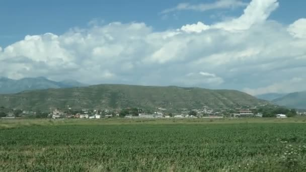 driving along a field next to Albanian city Finiq (in ancient times called Phoinike). Mountains and village in background