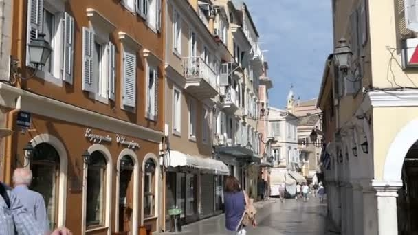 Corfu town, Corfu / GREECE May 31 2018: Group of People walking through the old town part of Corfu Town (Greece) on Sightseeing tour. Small streets and traditional houses with bars and stores all along.
