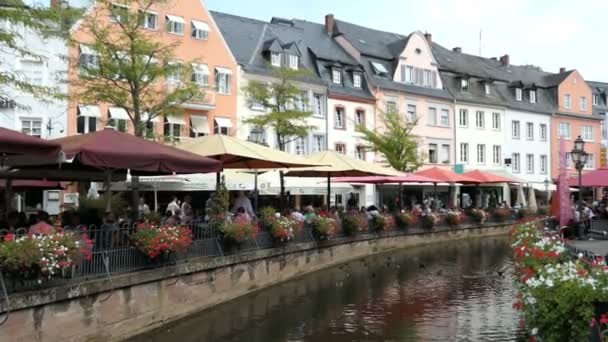 Saarburg,  Rhineland-Palatinate / GERMANY August 24 2018: Cityscape of Saarburg with its historical old town part and Leuk River flowing into the city towards the ancient mills. People sitting in bars and restaurants long the canal.