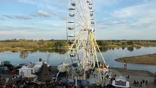 Tangermuende, Saxony-Anhalt / GERMANY September 08 2018: People visiting town festival names Burgfest in Tangermuende (Germany). Ferris wheel on promenade of Elbe river.