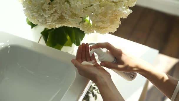 A lány összenyomja a hab, hogy mossa a kezét, és súrolja, higiéniai termék