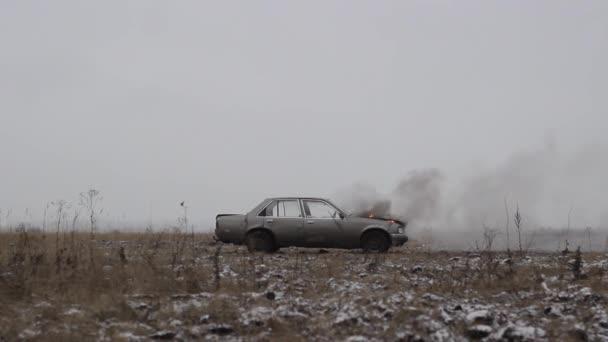 Unauto con un motore di masterizzazione è in piedi in un campo aperto, con tempo nuvoloso