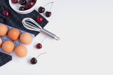 Raw Eggs Whisk Baking mold and checkered black napkin Ripe cherries Minimal Picture White Background Kitchen Supplement Copy Space Preparation Cooking Baking Kitchen Table Top view
