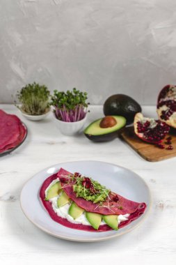 Tasty appetizing beetroot pancakes served on plate with avocado,