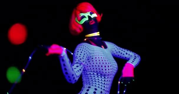 sexy Disco-Tänzerin posiert im UV-Kostüm