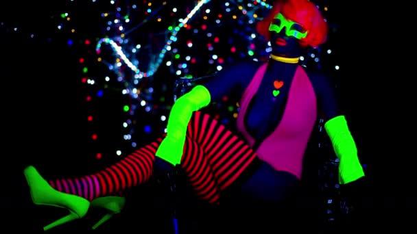 sexy weibliche Disco-Tänzerin posiert in fluoreszierendem UV-Kostüm