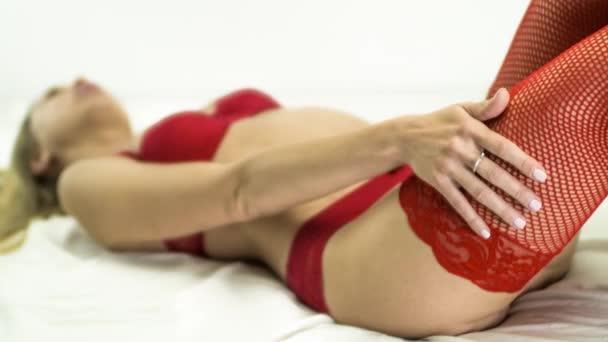 atemberaubend sexy junge Frau posiert in roten Dessous auf Bett