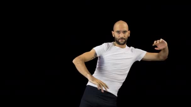 Skillful male dancer in white tshirt dancing on black background