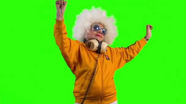 dancing older woman with headphones on green background