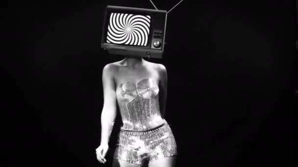 amazing woman in metallic costume dancing and posing with a television as a head. the tv is has a hypnotic video looping on it