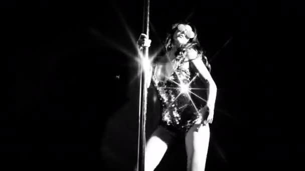 Amazing pole dancer in sparkling costume moving on black background