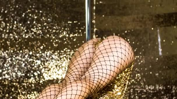 Body and legs of pole dancer in golden sparkling costume