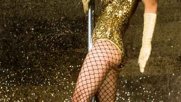Body of pole dancer in golden sparkling costume