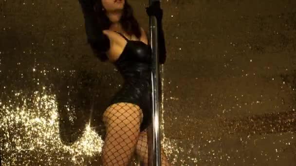 Pole-Tänzerin posiert im Kostüm mit Hasenohren auf goldenem Glitzerhintergrund