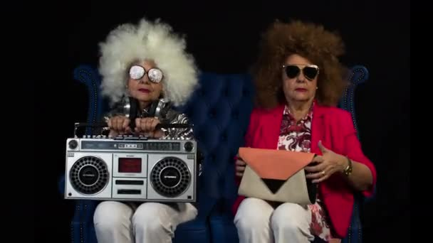 amazing grandma DJ, older lady with a ghettoblaster, partying in a disco setting. this version, she has been filmed twice to make two characters