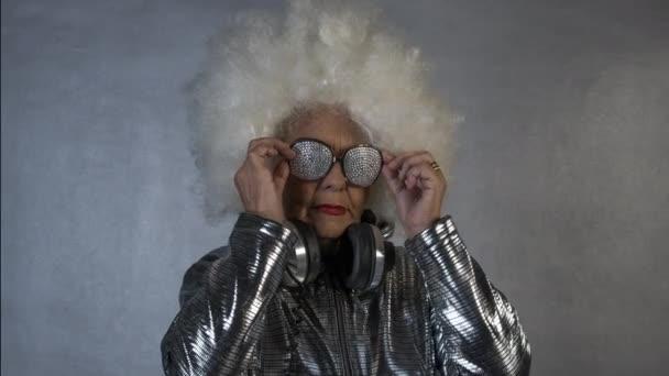 Amazing grandma in headphones and glasses