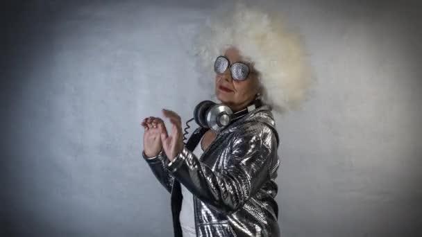 Amazing grandma in glasses and headphones dancing