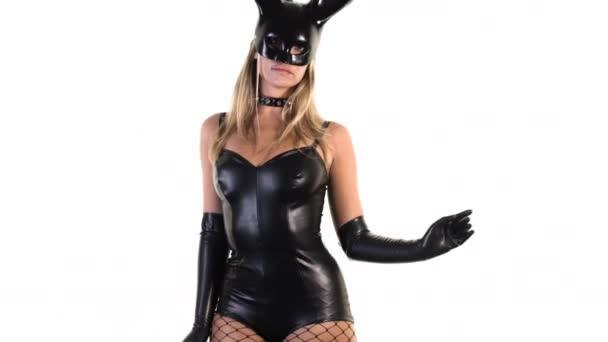 Vonzó nő, fehér alapon fekete latex test és nagy nyuszi füle maszk tánc