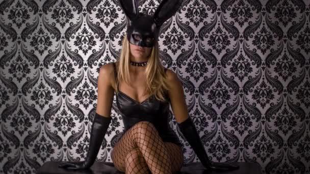 sexy Frau posiert mit großer Hasenohren-Maske und schwarzem Latex-Körper