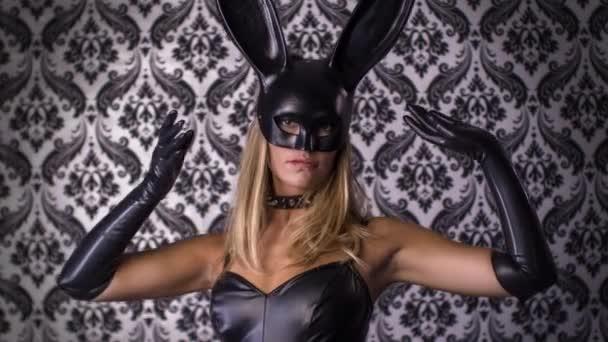 sexy Frau tanzt mit großer Hasenohren-Maske und schwarzem Latex-Körper