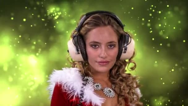Woman dancing in Santa Claus costume and headphones on green background