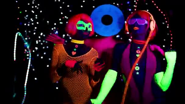 Sexy women and man with record vinyl head in fluorescent clothing under UV black light.