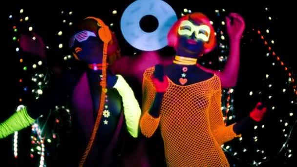 sexy Frauen und Männer mit Plattenschallplatte in fluoreszierender Kleidung unter UV-Schwarzlicht.
