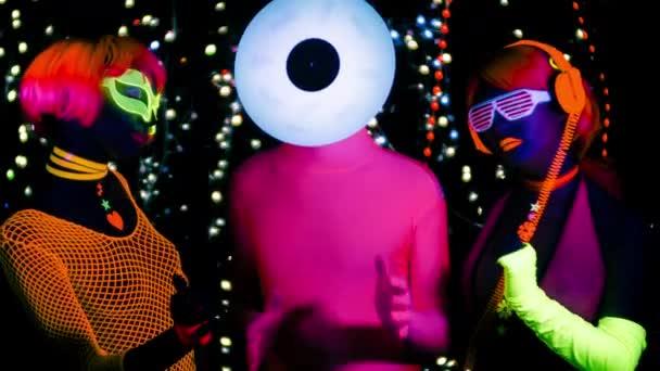Sexy ženy a muž s hlavou rekordní vinyl v fluorescenční oblečení pod Uv světlem černé.