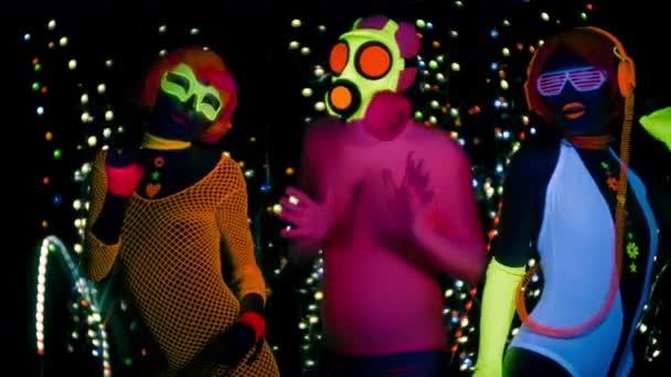 Sexy ženy a chlap v plynovou masku v fluorescenční oblečení pod Uv světlem černé