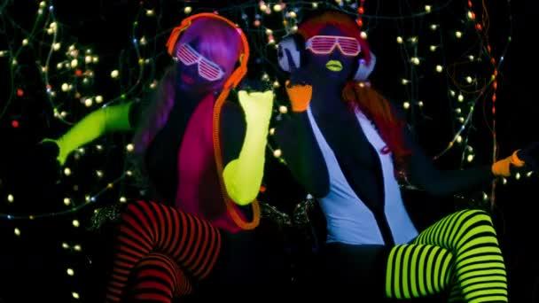 sexy Frauen in fluoreszierender Kleidung tanzen unter UV-Schwarzlicht auf schwarzem Hintergrund