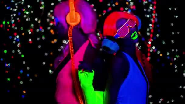 sexy Frauen in fluoreszierender Kleidung tanzen und posieren unter UV-Schwarzlicht.