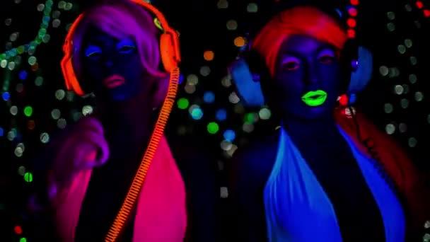 sexy Tänzerinnen in fluoreszierender Kleidung posieren unter UV-Licht.
