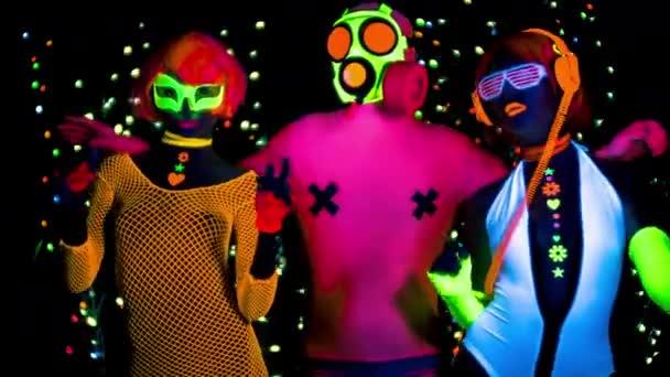 Két nő és férfi gázálarc és fluoreszkáló ruha tánc