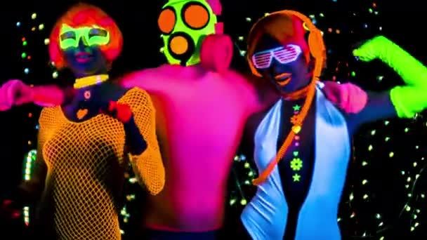 zwei Frauen und ein Mann in Gasmaske und fluoreszierender Kleidung tanzen