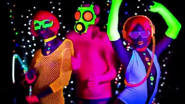 A nők és a srác a gázálarc, a fekete Uv-fényben fluoreszkáló ruházat