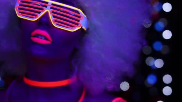 Disco-Tänzerin posiert in fluoreszierendem Kostüm und riesiger Afro-Perücke