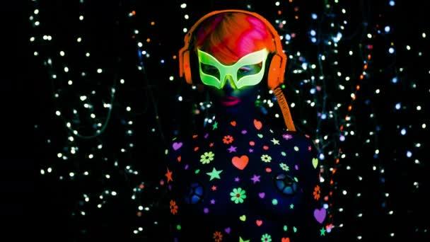 Fiatal, vonzó nő a fluoreszcens üvegek és fejhallgató fekete Uv-fényben