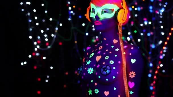 junge attraktive Frau in fluoreszierender Brille und Kopfhörer unter UV-Schwarzlicht