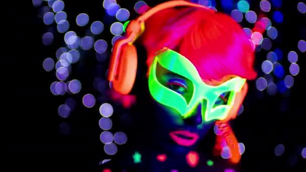 Fantasztikus szexi nő, a fluoreszcens üvegek és fejhallgató fekete Uv-fényben