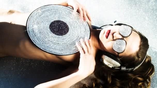 attraktive junge Frau posiert mit glänzender Schallplatte auf dem Boden