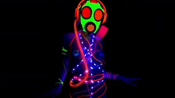 uv fluoreszierende Gogo-Tänzerin tanzt mit Gasmaske
