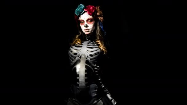 beautiful woman with custom designed candy skull mexican day of the dead face make up on black background
