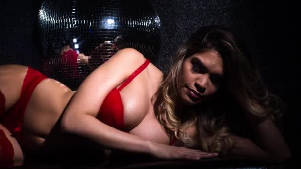 Atraktivní žena pózuje v červené spodní prádlo pod disco koule