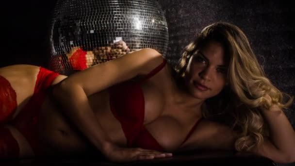 Attractive woman posing in red lingerie under disco ball