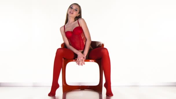 Sexy woman posing in red lingerie on red chair
